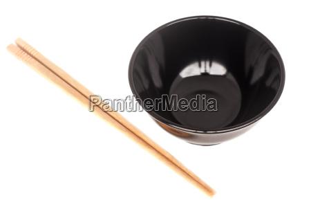 black ceramic bowl with wooden shopsticks