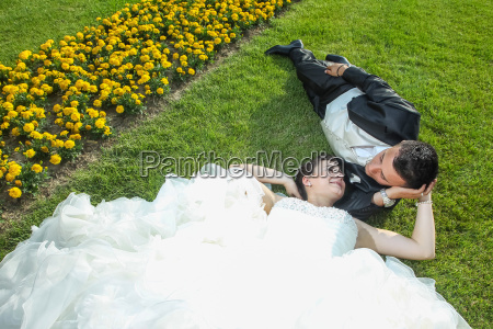 bride and groom lying down on
