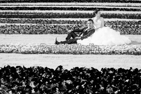 bride and groom sitting on lawn