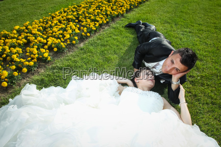 newlyweds lying down on lawn with