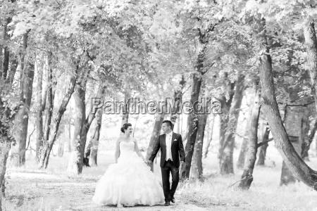 newlyweds walking in nature bw