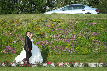 newlyweds walking on pathway with flowers