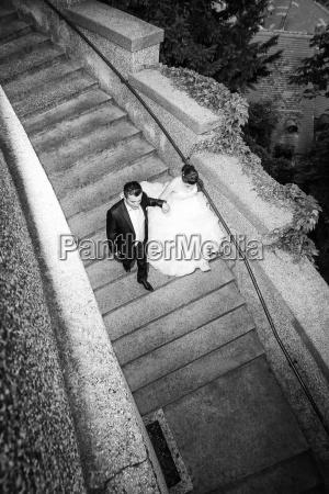 newlyweds walking down stone steps bw