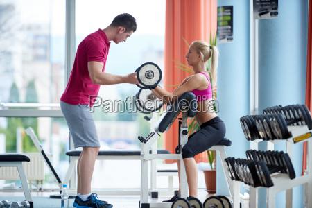 junge sportliche frau mit trainer uebungsgewichte