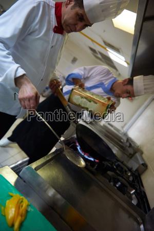 kuechenchef in hotelkueche bereiten essen mit