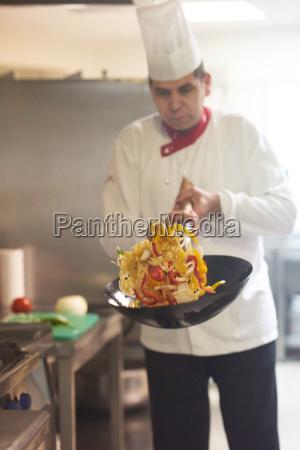 chef in der hotelkueche bereiten nahrung