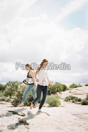 two women running barefoot across the