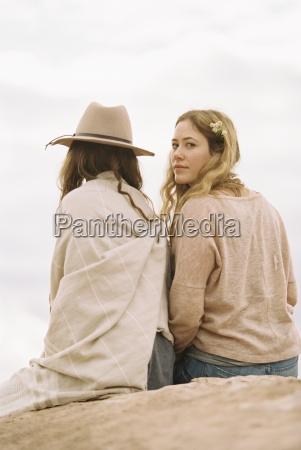 two, women, sitting, side, by, side - 14713525
