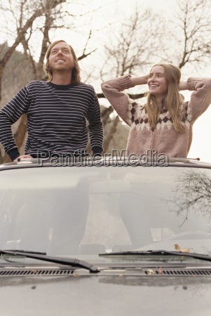 young couple standing in their car