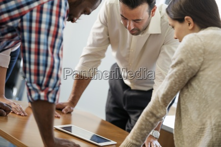 four people leaning on a table