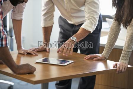 vier menschen lehnt auf einem tisch