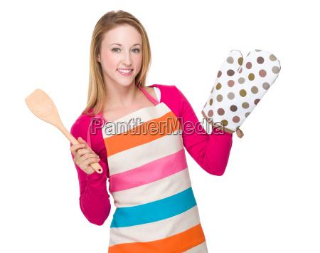 junge hausfrau heben ofenhandschuhe und holzloeffel