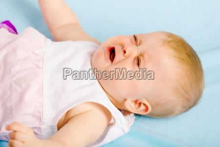 schreiendes baby auf plaid liegen