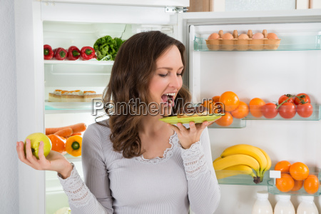 woman with apple eating donut