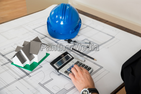 architect with blueprint calculating on calculator