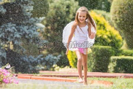 girl with angel wings running around