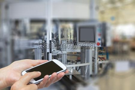 haende und smartphone in industriell innen