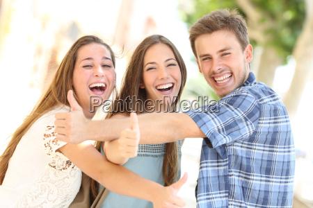 drei glueckliche jugendliche mit den daumen