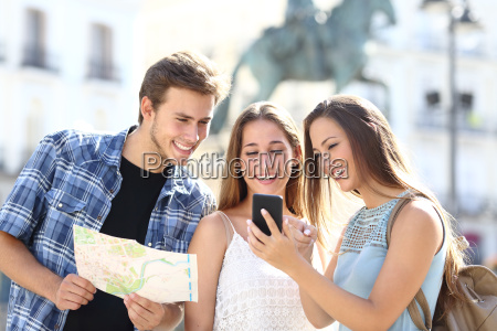 three tourist friends consulting gps on