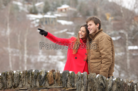 couple crossing a bridge in winter