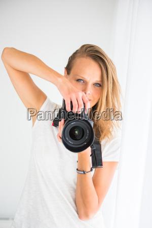 huebsche weibliche fotografin mit digitalkamera