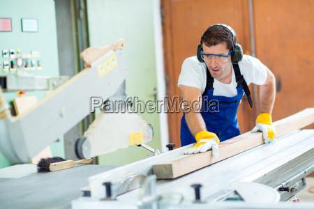 two worker in workshop using saw