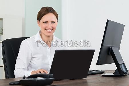 geschaeftsfrau arbeitet auf laptop und desktop