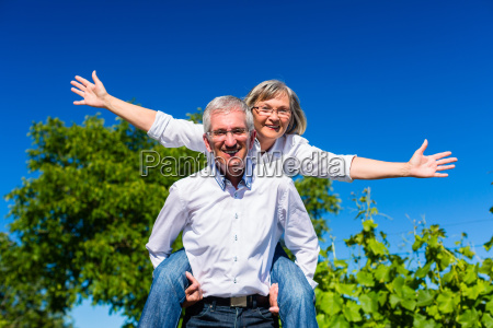 senior man carrying woman on his