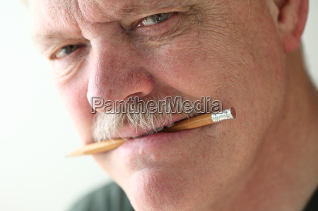 man holds pencil in mouth