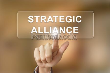 business hand clicking strategic alliance button
