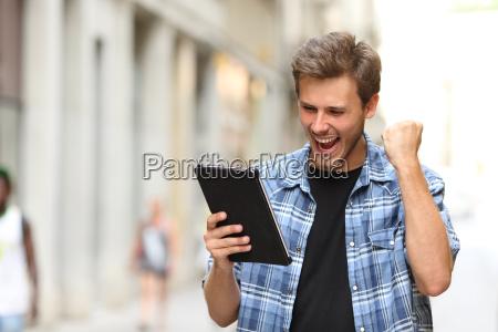 euphoric gewinner mann mit einem tablet