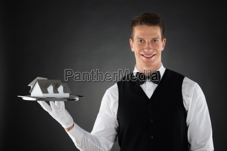waiter holding tray with house model