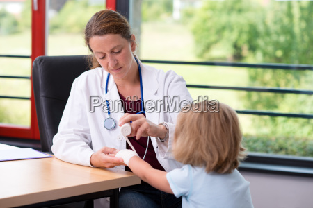 female doctor bandaging the arm of