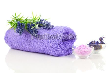 handtuch mit lavendelblueten und aromabad salz