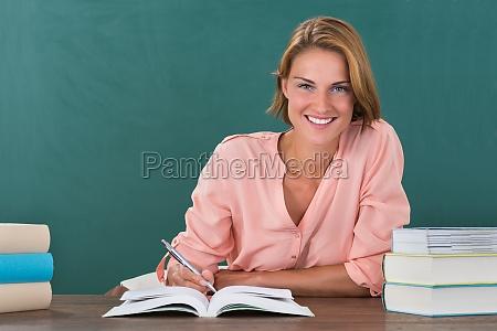 weiblicher lehrer studium am schreibtisch