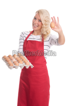 woman in apron holding an egg