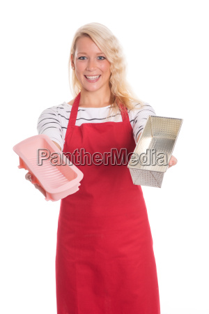 housewife in apron holding different bakeware