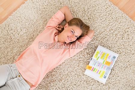frau mit tagebuch liegen auf teppich