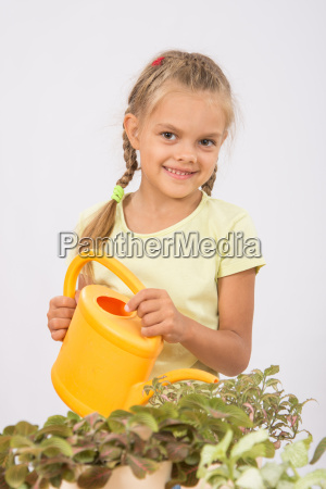 happy little girl watering flowers watering