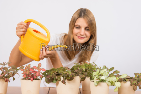 happy girl watering potted plants from