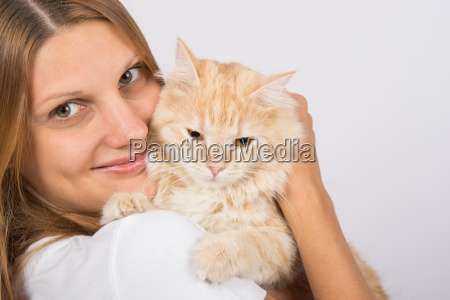 maedchen umarmt einen veraergerten katze