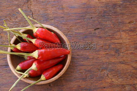 fresh chili peppers in small wooden