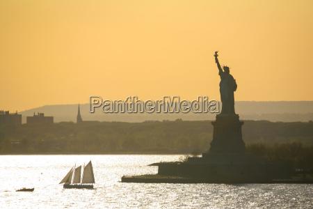 sailboat next to statue of liberty