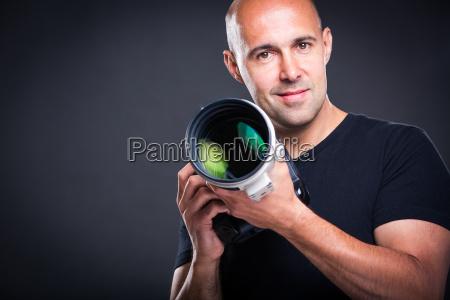 junger maennlicher profifotograf in seinem studio