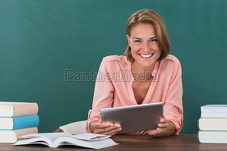 lehrer mit buechern und digitale tablet