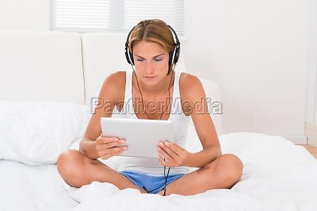 woman using headphones and digital tablet