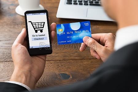 unternehmer mit kreditkarte und handy