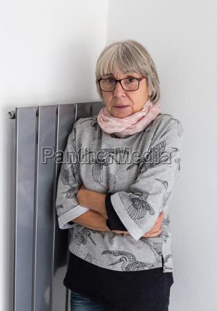seniorin steht frierend vor defekter heizung