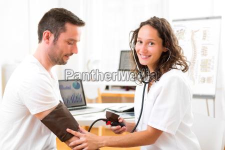 junge attraktive arzt ueberpruefung des patienten
