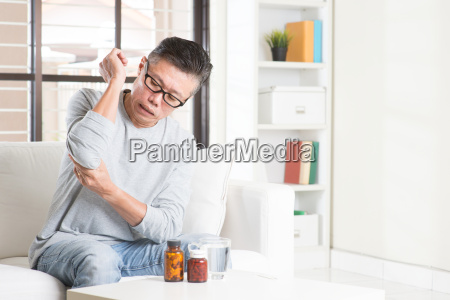 mature asian man elbow pain